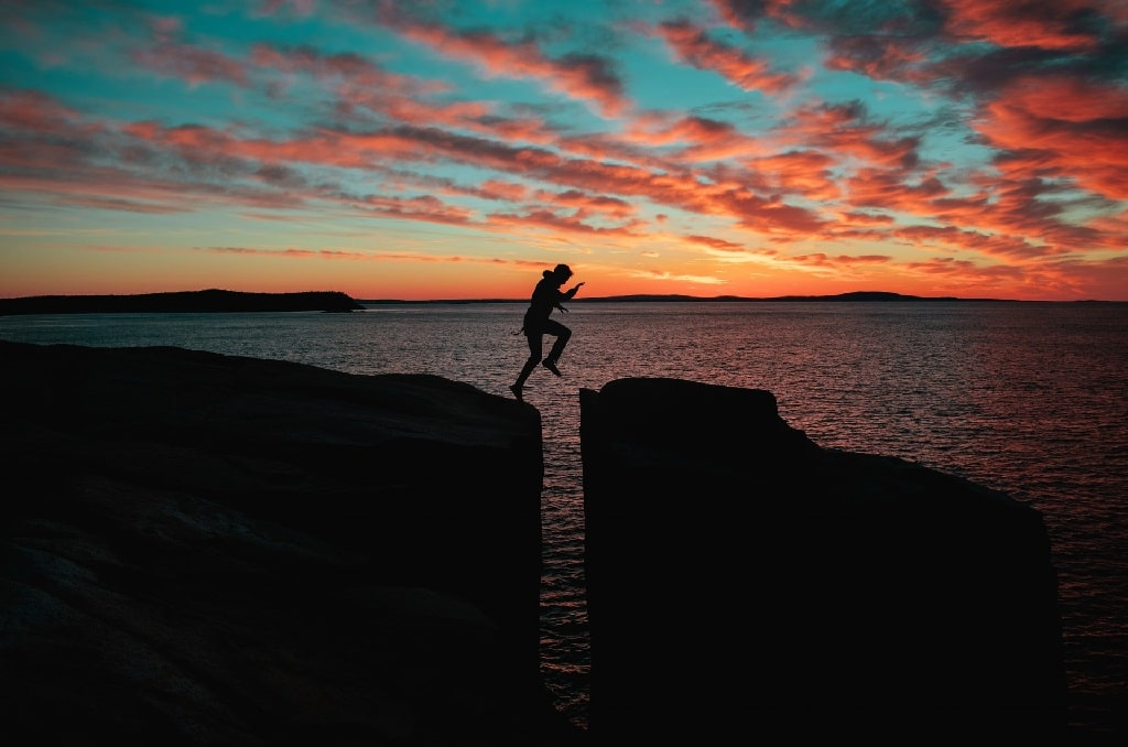 man jumping over rocks at sunset, why bad psychedelic trips are important