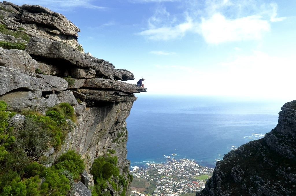man sitting on cliff ledge, psychedelic dangerous behavior