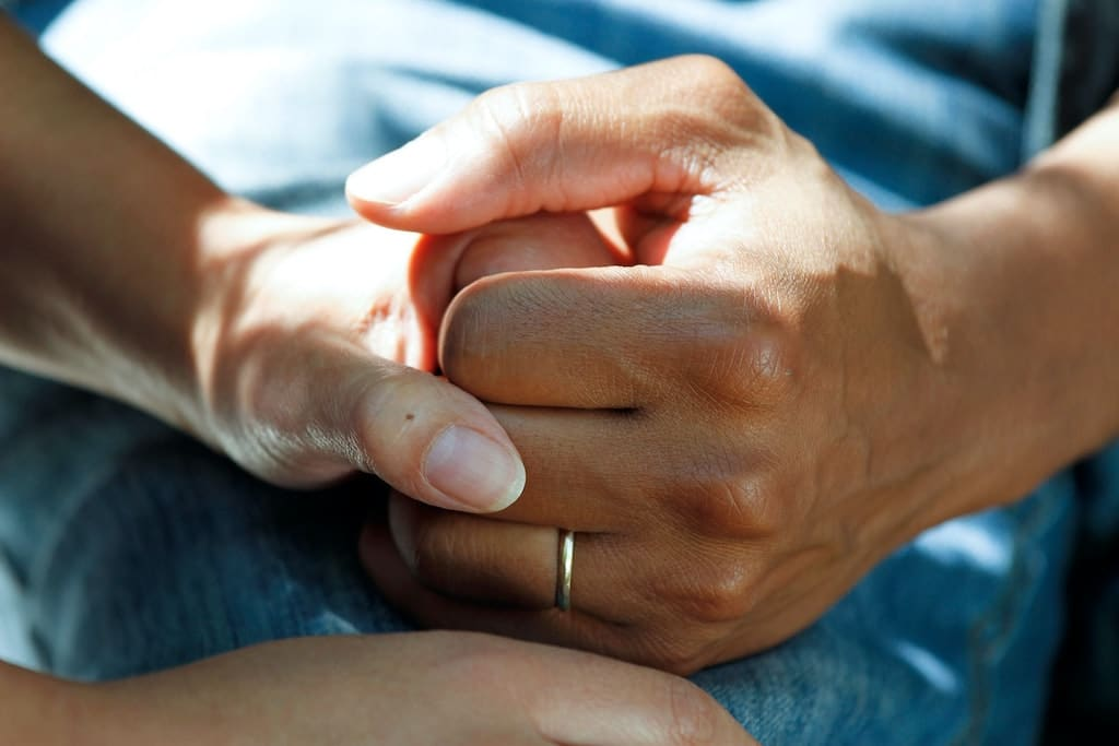two people holding hands, is psychedelic assisted therapy legal