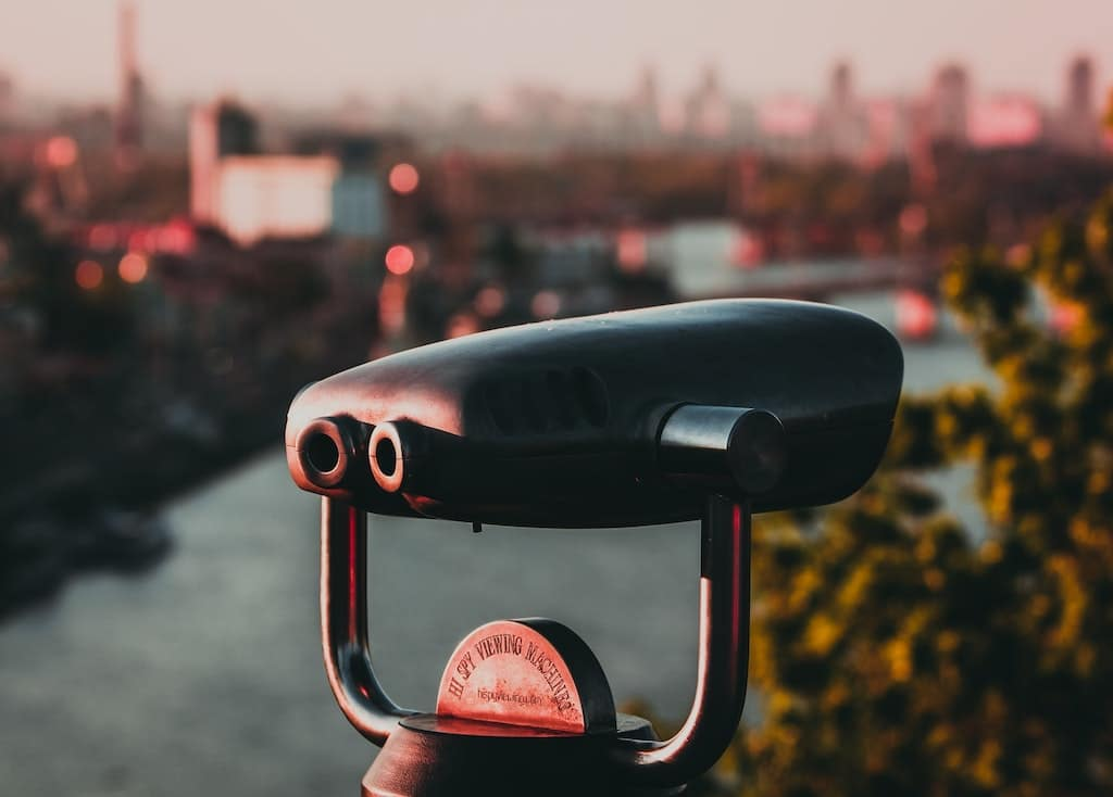 binoculars with city in background, finding psychedelic assisted therapy