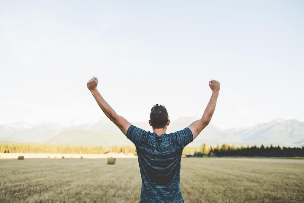 man raising arms in field, psychedelic assisted therapy vs integration