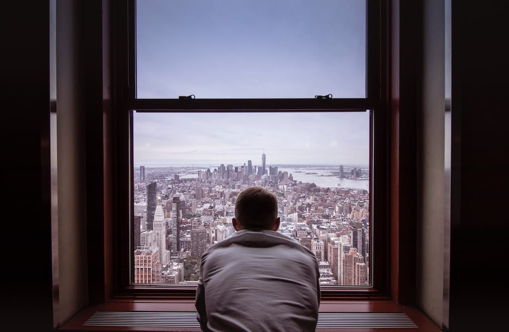 man looking out of NYC window, how psychedelics work in the brain