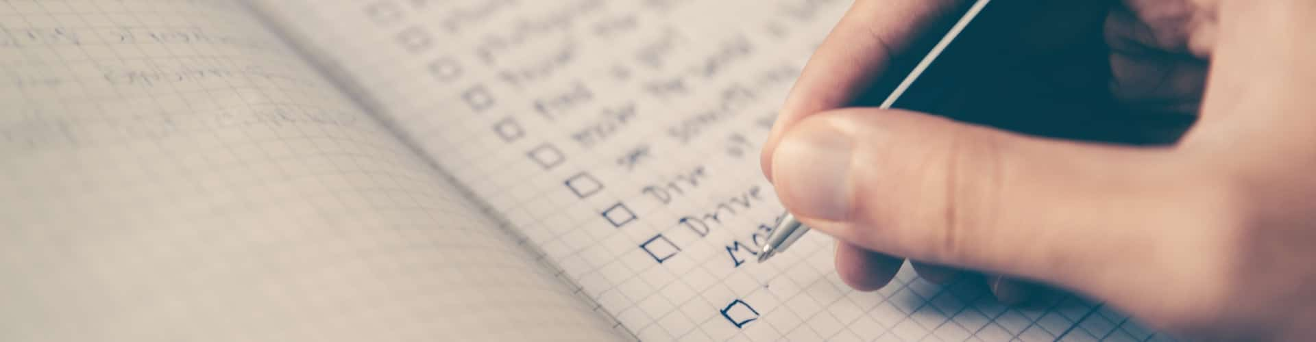person writing checklist in notebook, what to look for in a psychedelic therapist