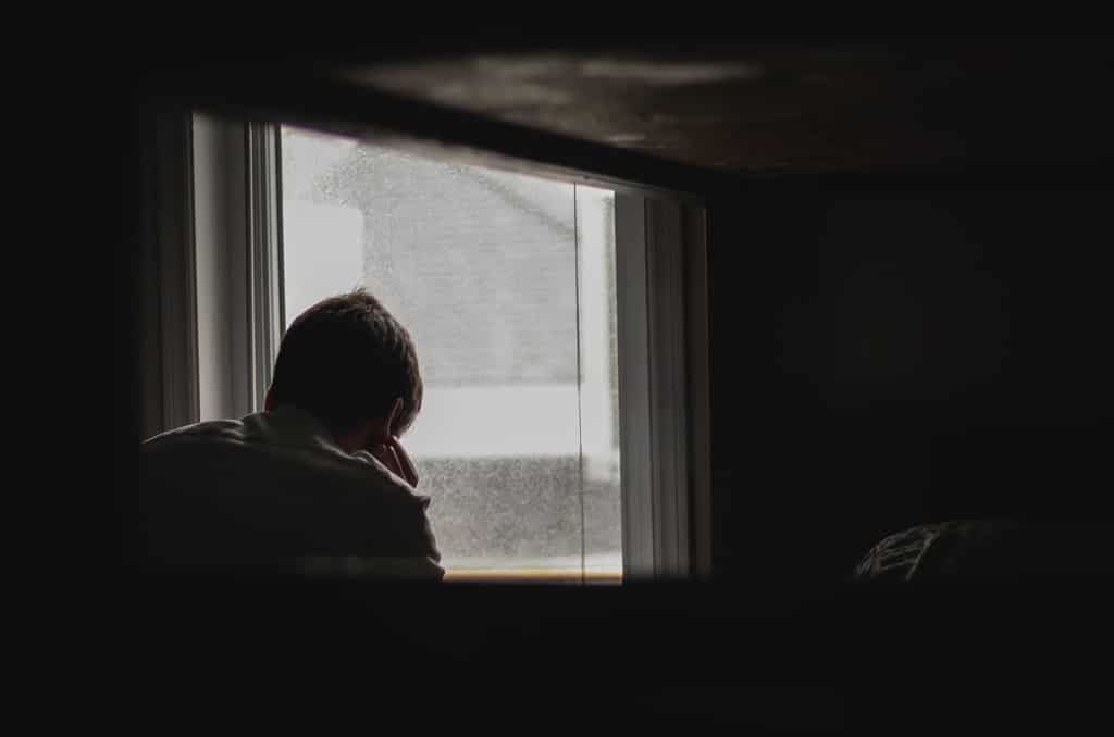 man near window in dark room, psychedelics and ptsd treatment