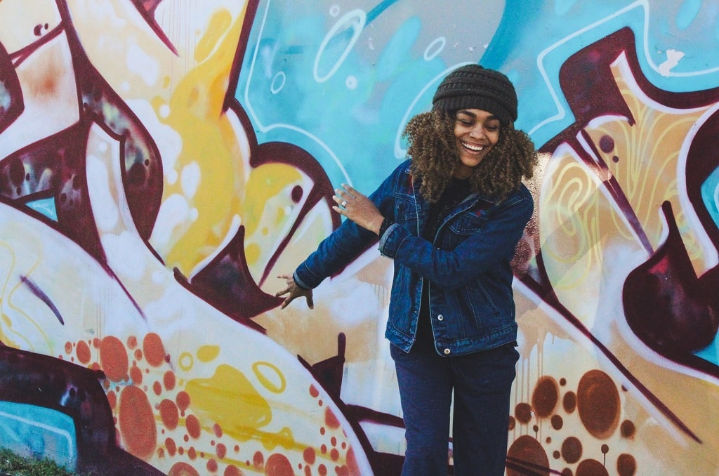 happy black woman standing in front of graffiti, proper age to start psychedelic exploration