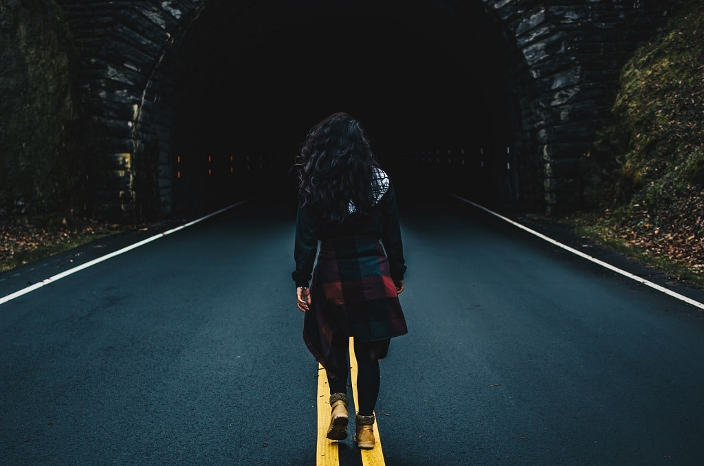 woman walking into dark tunnel, psychedelic bad trips can be meaningful
