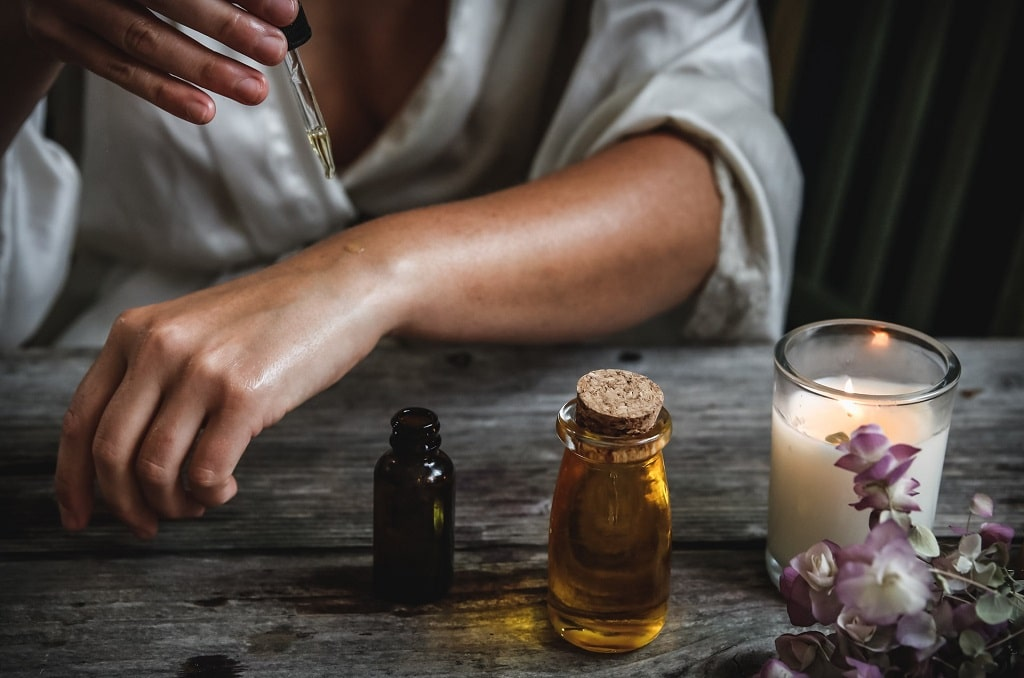 woman putting tincture on her arm, what does cannabis treat