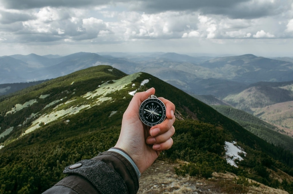 hand holding compass on mountain, use psychedelics for transcendental healing
