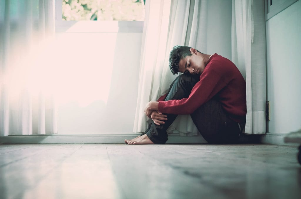 man curled in corner of room, what is cannabis assisted psychotherapy