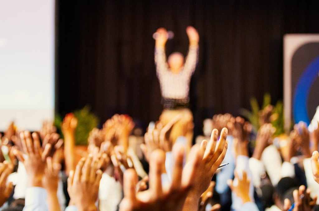 crowd with hands raised, attend a cannabis conference