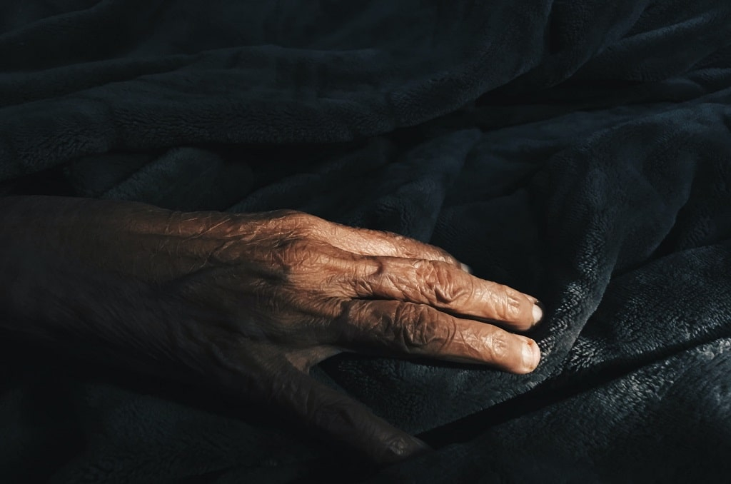 elderly hand on bed, psychedelics help end of life care