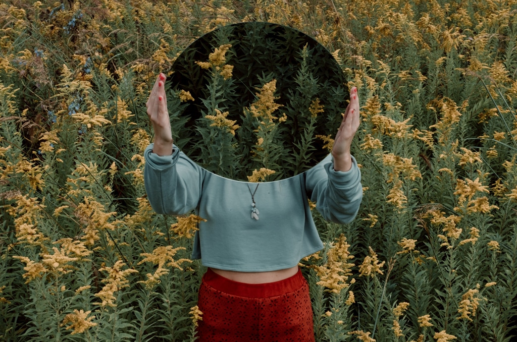 woman in flower field holding mirror, set and setting for psychedelic experiences