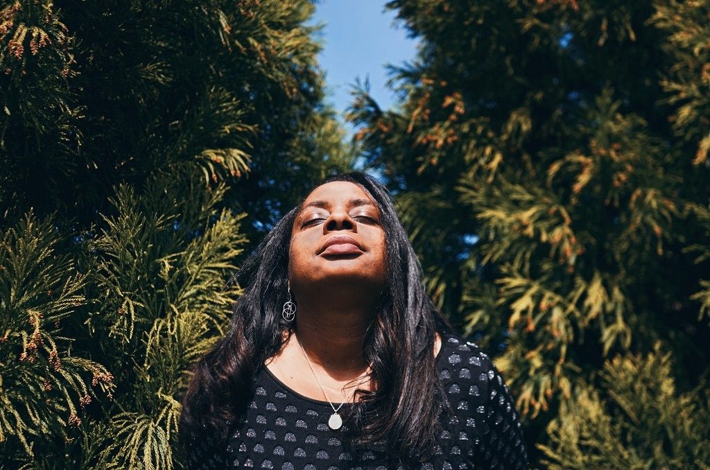 woman eyes closed head raised toward sky, what is cannabis assisted psychotherapy like