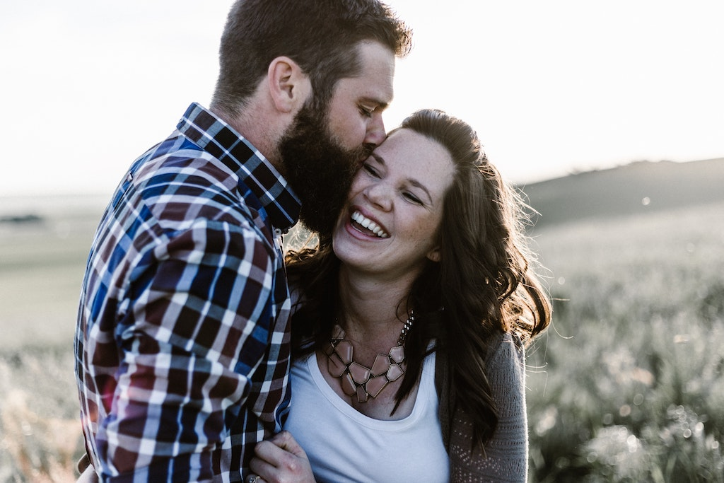 man kissing woman in field, how can psychedelics benefit happy people