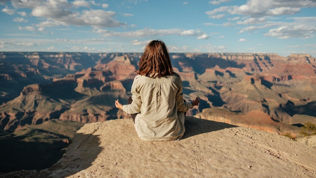 woman meditating on cliffside, how to enter psychedelic realm without drugs