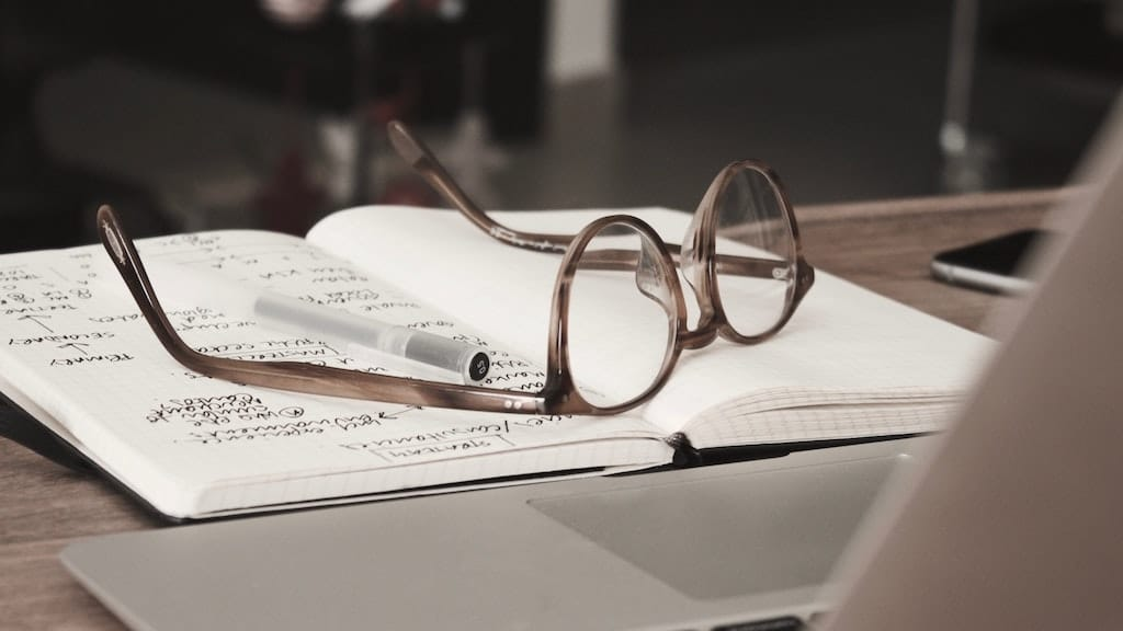 open notebook with eye glasses, relationship between humans and psychedelics