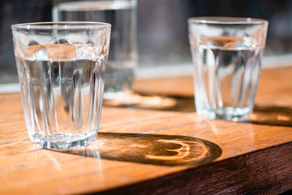 two glasses of water on wooden table, how ketosis fasting impacts the psychedelic experience