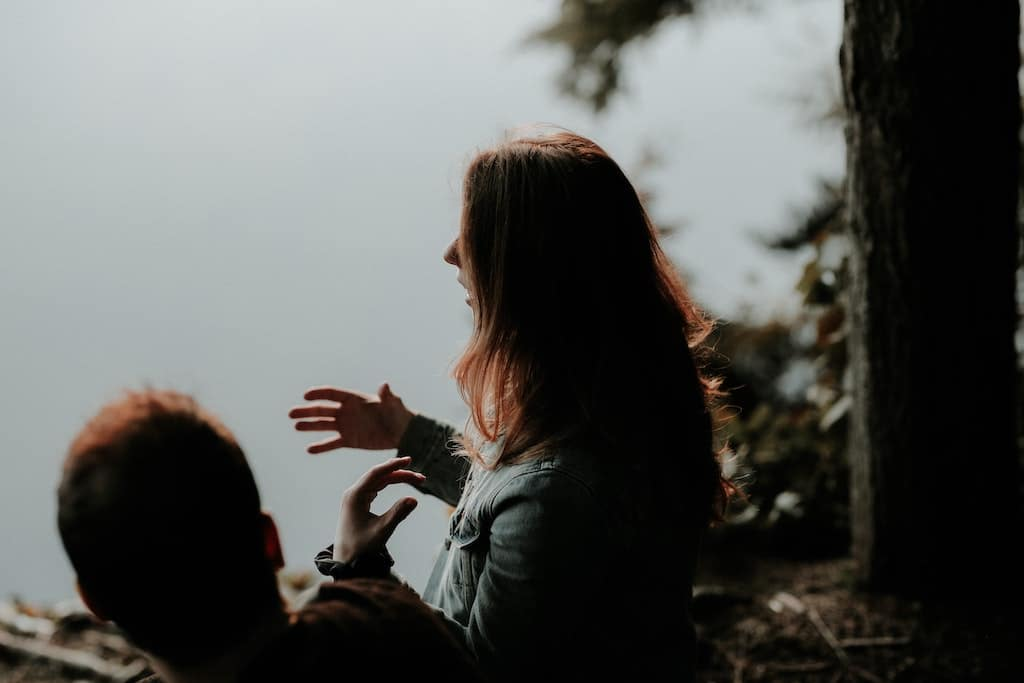 man and woman sitting and talking, what to look for in a psychedelic therapist