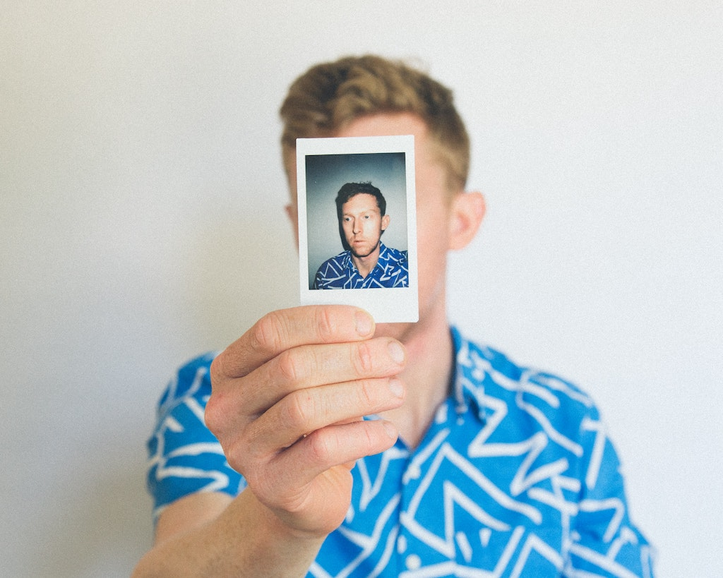 man holding up photo of himself, 5 reasons you might not trip on high doses of psychedelics