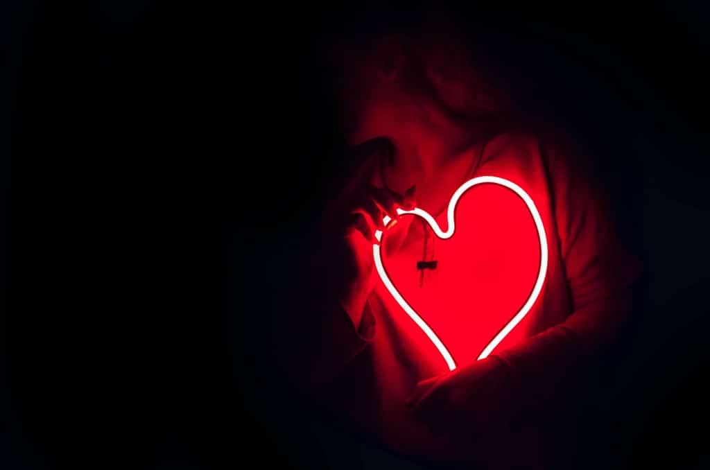 woman holding red neon heart, psychedelic healing potential