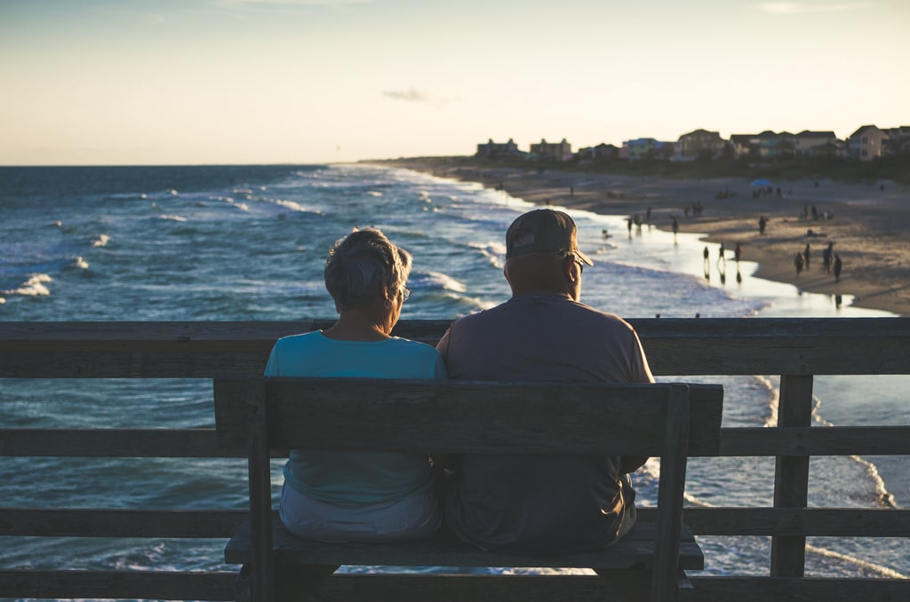 elderly couple sitting on bench at pier, psychedelic reform and timing