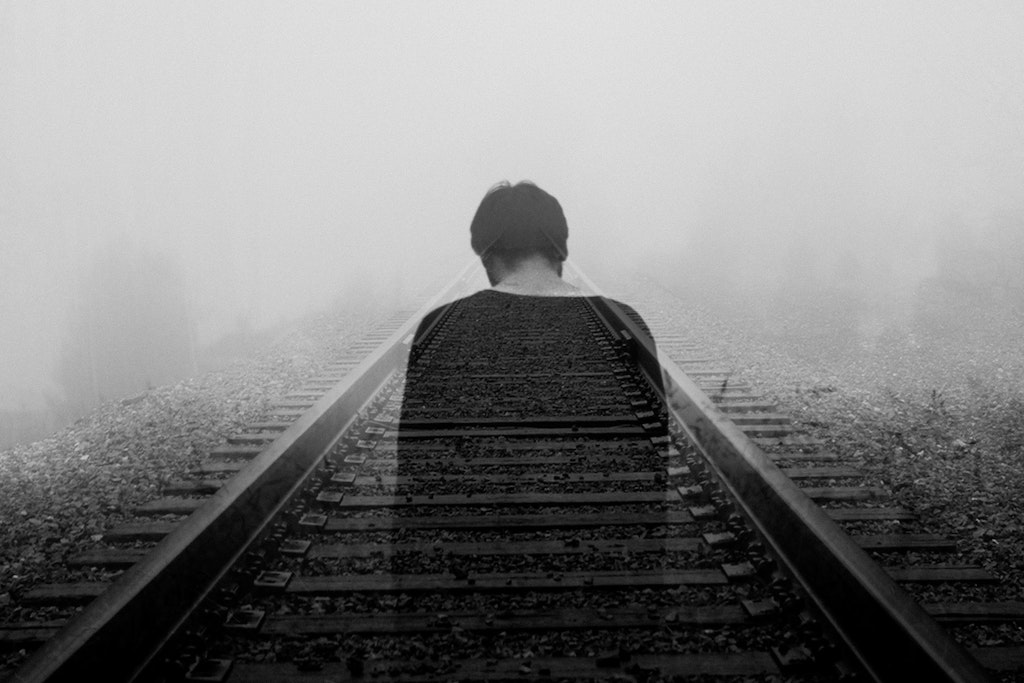 man walking along railroad tracks, how psychedelics can help treat anxiety
