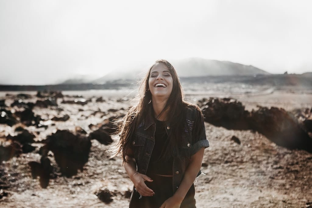 smiling woman at beach, how psychedelics can help treat anxiety